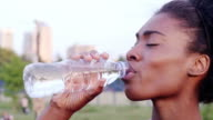 CU  Handheld slow motion tired woman athlete drinking water and looking to camera