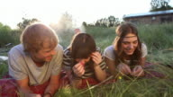 CU, Handheld, three friends lying on their fronts, tickling each other with grass
