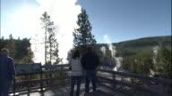 Hand-held track forward behind park ranger walking along wooden walkway towards observation deck overlooking steaming geyser in Norris geyser basin