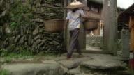 Hand-held track forward following woman carrying baskets on pole along walkway in Ping'an village, Guilin, Guangxi Zhuang