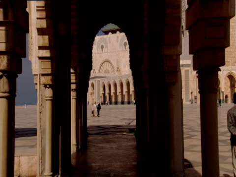 Handheld track forward through arches towards mosque and tower Hassan II Mosque Casablanca