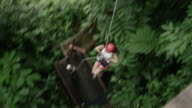Handheld wide shot of woman ziplining in rain forest / Quepos, Puntarenas, Costa Rica