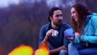 MS handheld young couple eating and chatting by camp fire seen through flames