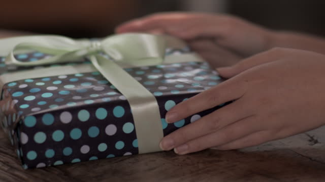 CU handheld young woman opening present