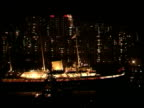 Handover events NAT ITN HONG KONG Victoria Harbour NIGHT Royal yacht Britannia sailing along with litup skyscrapers in b/g Convention Centre GV...