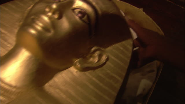 Hands close a pharaoh's sarcophagus.