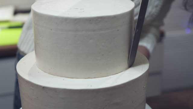 Hands creating a thin and uniform layer of wedding cake using palette-knife