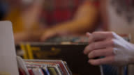 Hands flip through stacks of vinyl records in music shop