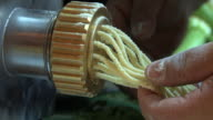Hands gently pull fresh pasta from a machine.