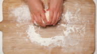 CU Hands kneading dough in flour on wood surface / Seoul, South Korea