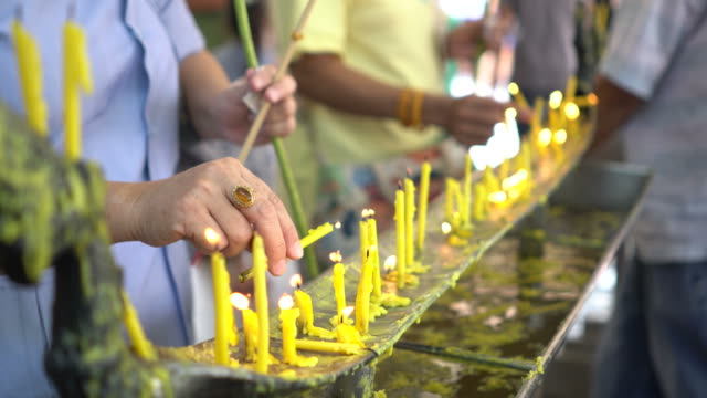 Hands Lighting Candles at Buddhist Temple in Chiang Mai, Thailand