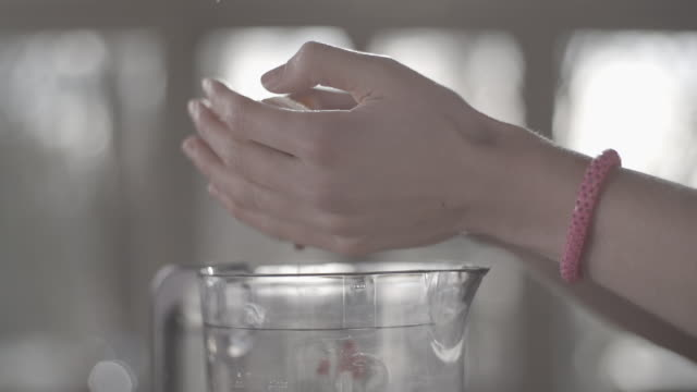 C/U SLOMO hands making a fruit milkshake w/ mixer