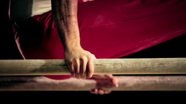 SLO MO Hands of a male gymnast training on parallel bars