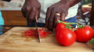 Hands of African American man chopping tomato on cutting board