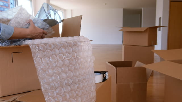 Hands of Asian woman wrapping vase with bubble wrap