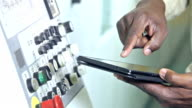 Hands of black man at control panel with digital tablet