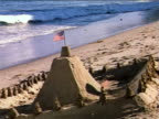 1959 hands of boy on beach molding sand wall around sand castle with small American flag / industrial