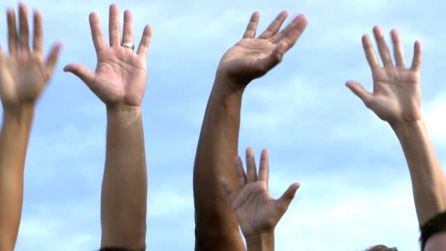 Hands of boys and men raised to volunteer