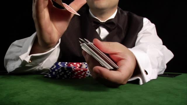 Hands of casino dealer shuffling cards on table