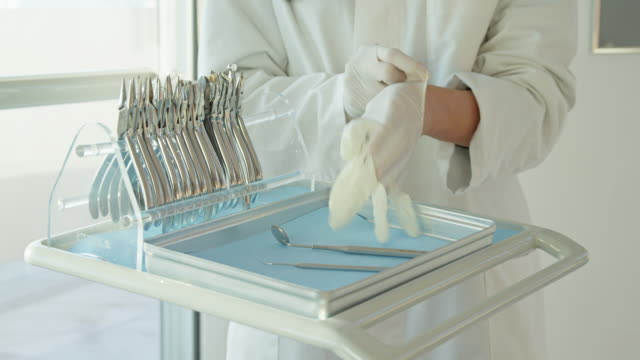 CU hands of female doctor putting on surgical gloves
