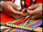 Hands of Inca woman in traditional clothing weaving colourful materials, Peru