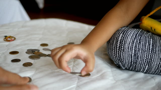 Hands of little girl counting coins
