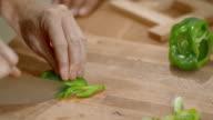 Handen van mannelijke chef-kok snijden groene peper op een houten snijplank