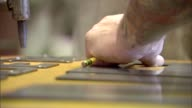 CU hands of male workers measuring with ruler outlining w pencil and lining up metal letters on yellow board pan to file as it is rubbed against tip...