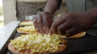 Hands of person adding toppings to pizza bases.