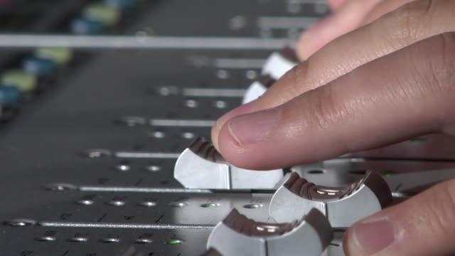 ECU Hands of sound engineer adjusting volume on mixing console / New York City, New York, USA