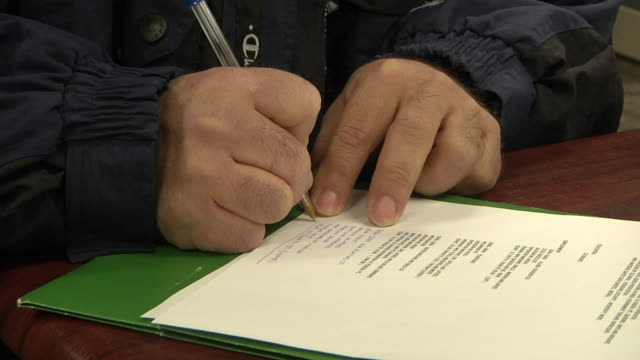 CU ZI Hands of unemployed worker filling out paperwork and applications at Michigan Works job center, Jackson, Michigan, USA