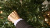 CU Hands on man decorating Christmas tree with fairy lights / New York City, New York, USA