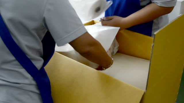 Hands packing goods into box
