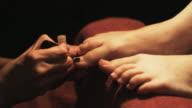 hands painting toenails