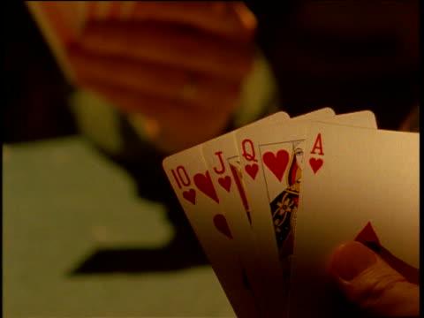 Hands pick up King in poker game making a Royal Flush