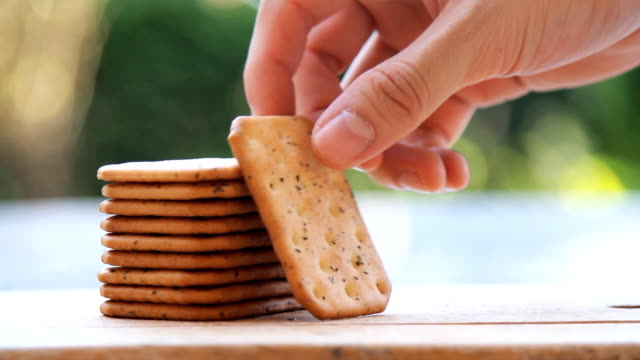 hands picking up a stack of cracker