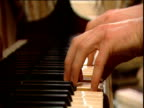 Hands playing on piano keyboard