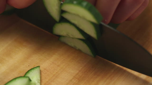 ECU R/F TS Hands slicing Cucumber with knife on cutting board / Seoul, South Korea
