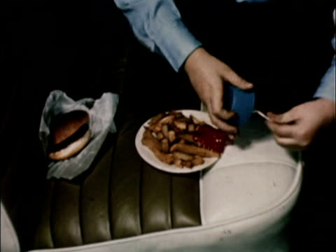 1956 CU Hands spooning out ketchup onto plate of French fries sitting on leather car seat / USA