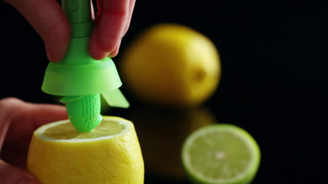 CU Hands squeezing lemon with kitchen utensil on cutting board / Seoul, South Korea