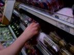 Hands stack supermarket shelves with packaged fruit and vegetables