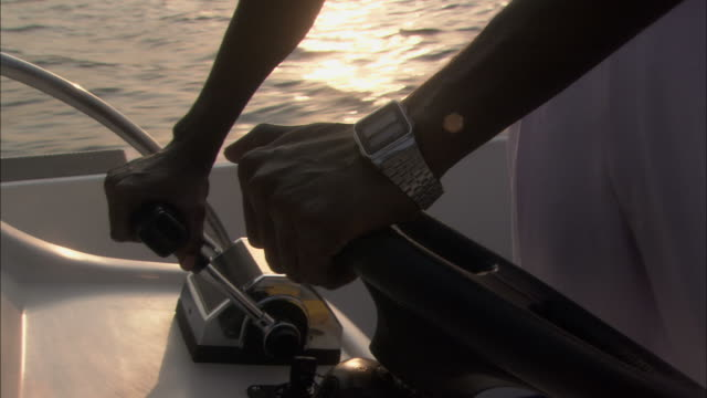 Hands steer wheel of speed boat Available in HD.