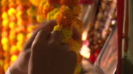 Hands tie marigolds together by their stems to form garlands.