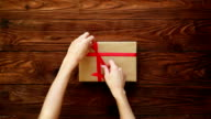 Hands tied the gift box with a red ribbon