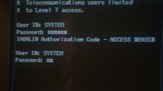 Hands type on a computer keyboard, with access denied appearing on the monitor.