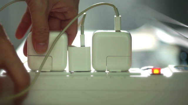 Hands unplug many adaptor from electrical outlet and turn off electricity switch at home.