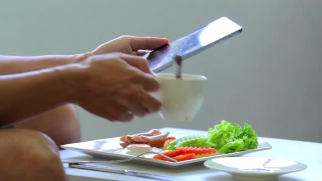 Handen met behulp van digitale tablet met ontbijt, time-lapse