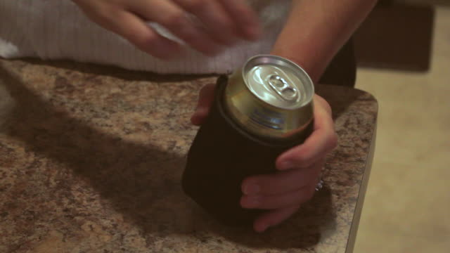 Hands with light complexion opening aluminum drink can on coozie on marble countertop