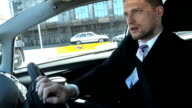 Handsome businessman is driving a car.