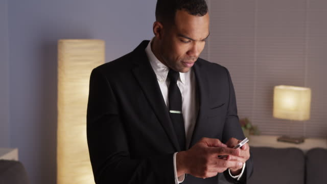 Handsome businessman typing on smartphone
